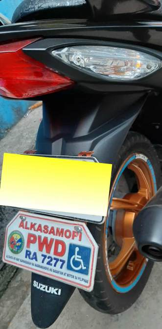 A personalized plate number is attached to the motorcycle to notify enforcers that the rider is a PWD and ALKASAMOPI member.